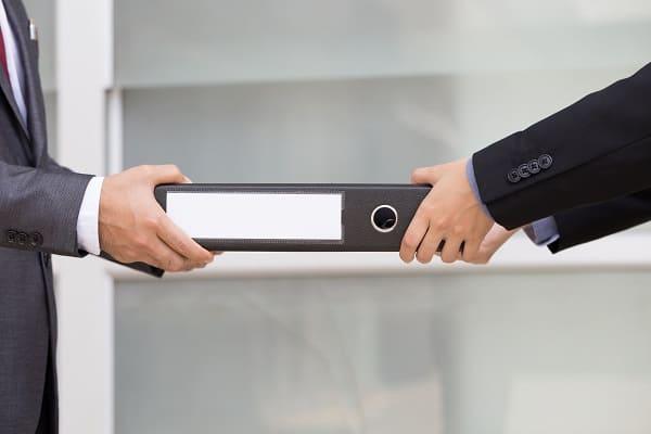 Zwei Personen, die zusammen einen Aktenordner halten oder übergeben.