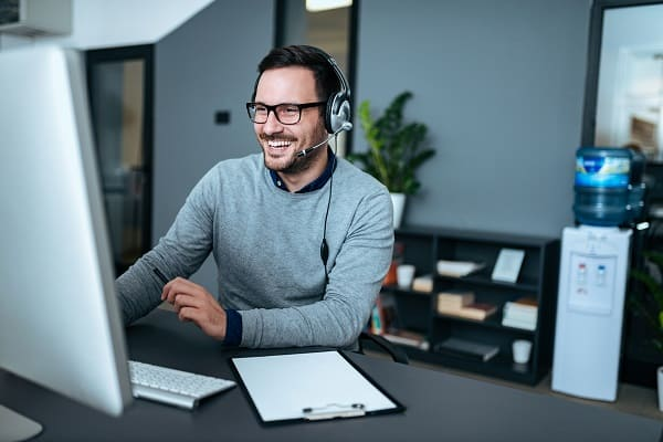 Ein junger fröhlicher Mann beim Telefonieren vor dem Computer