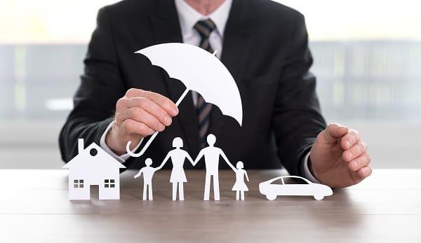 Ein Mann im Anzug Schütz mit einem Regenschirm symbolisch das Haus, die Famile und das Auto