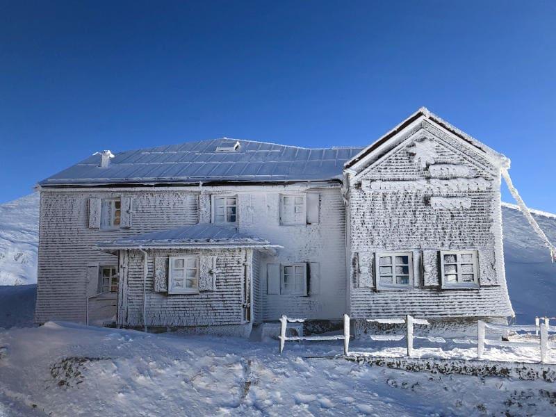 Ein Holzhaus verschneit und vereist auf dem Berg.